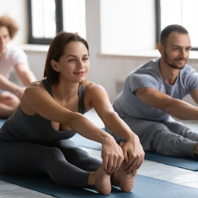 Happy woman stretching muscles in seated forward bend pose.
